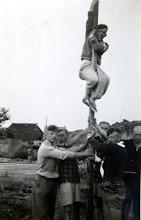 Photo: JB kamp Ameland 1957 Hendrik-Jan Homan klimt in de paal. Onderaan v.l.n.r. Roelof Vedder, Hendrik Hoving, Roel Drenth, Hendrik Witting en Hendrik Scheper