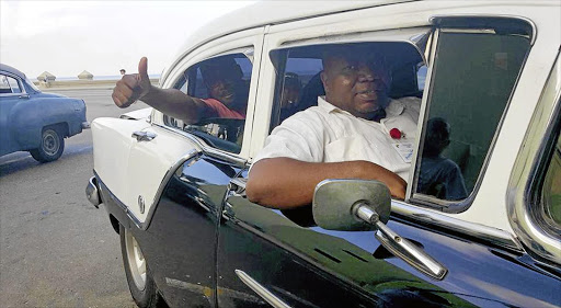 Reporter Mzwandile Mbeje, one of the 15 staffers sent to Cuba, admiring the country's famous old cars.