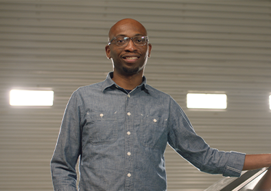 Founder Seyi Fabode smiles at the camera inside his garage-turned-office.