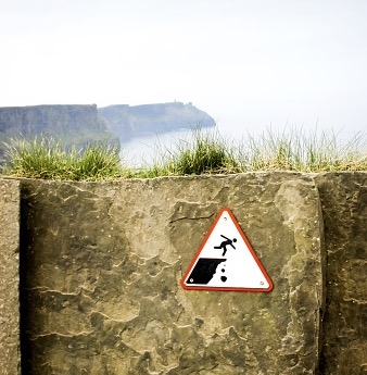 A sign on a low wall prevent people from falling off a cliff.