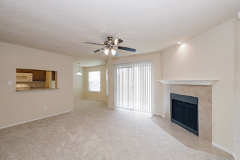 Carlisle living room with carpet, ceiling fan, and fireplace