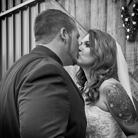 Kisses After And More To Come by Janice Mcgregor - Wedding Bride & Groom ( canon, wedding photography, kissing, b&w, black and white, canon sl1, love, smooches, married, tuxedo, that day, wedding, woman, outdoors, canon photography, special, bride and groom, bride, tattoo, groom, outside, man, kisses,  )