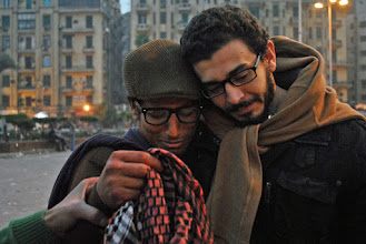 Photo: Two protesters arriving at the scene as day breaks mourn over a protester's bloody keffiyeh.