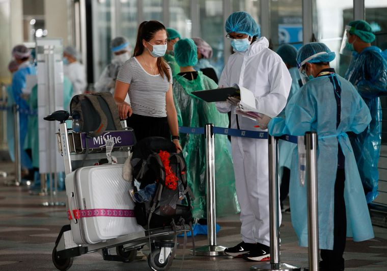 Проверка иностранки на коронавирус и подготовка ее к 14-дневному карантину в аэропорту Бангкока, Таиланд, 1 октября 2020 года.
