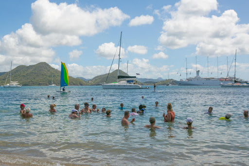 beach-bbq-scene.jpg - Windstar passengers loll in the placid waters of Pigeon Island, St. Lucia, during a beach barbecue.