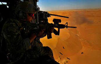 Photo: U.S. Air Force Pararescueman Alejandro Serrano from the 46th Expeditionary Rescue Squadron, and a machine gunner next to him, test fire their weapons in the open desert of Afghanistan's Kandahar province on Monday Oct. 11, 2010. The helicopter, flown by pilots from the 26th Expeditionary Rescue Squadron, flew over the red dunes in southern Kandahar province on their way to pick up two Afghan casualties.