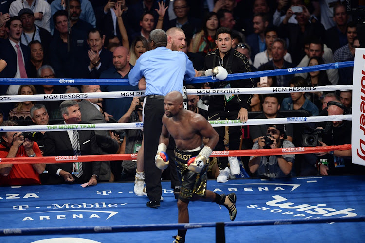 Floyd Mayweather Jr. (black trunks) celebrates after knocking out Conor McGregor (white trunks) during their boxing match at T-Mobile Arena. Mayweather won via 10th round TKO.