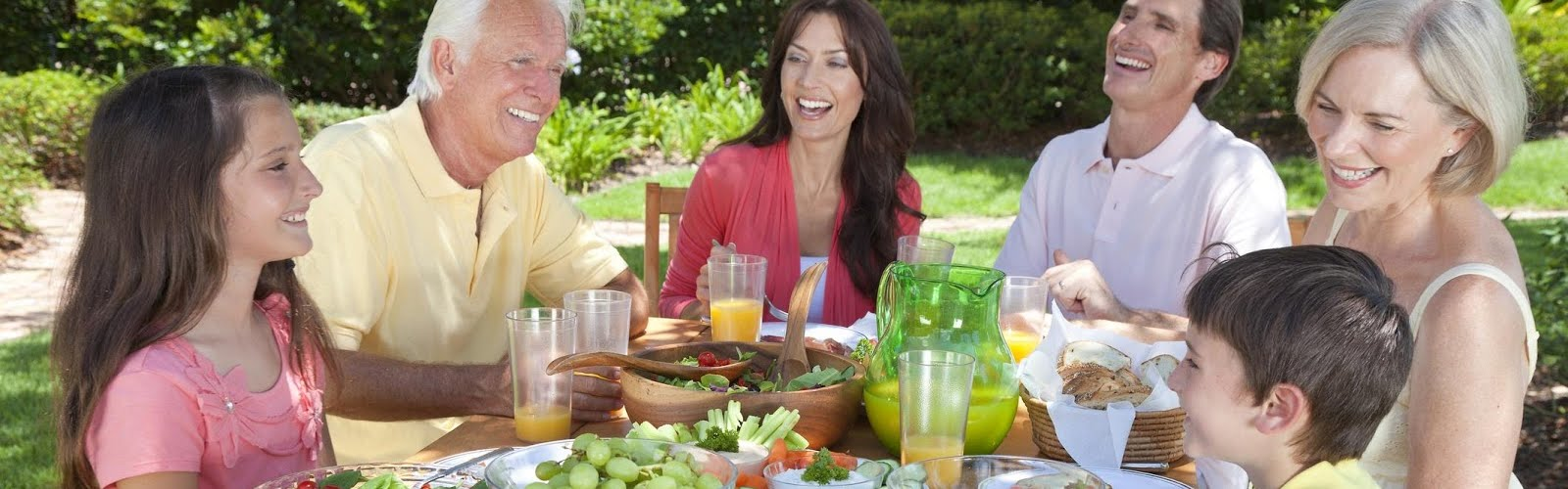 a family sitting around a table having a healthy lunch smiling with white teeth