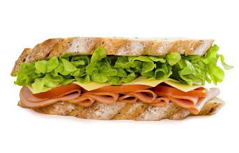 Photo: sliced virginian ham sandwich on gourmet multi-grain bread together with tomatoes, cheese and lettuce