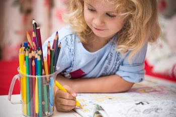 Little girl coloring in book