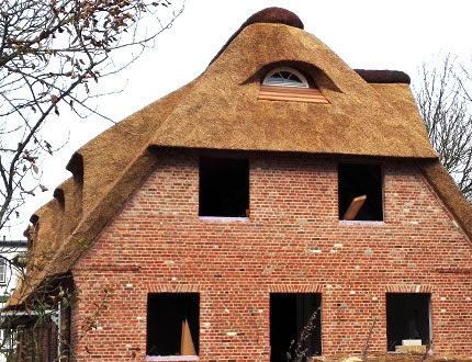 Ceglany dom bez okien kryty strzechą w trakcie remontu