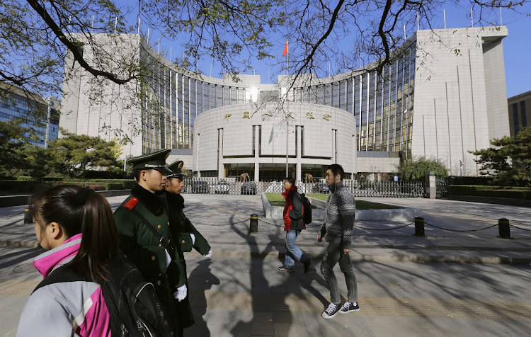 People walk past the headquarters of the People's Bank of China (PBOC), the central bank, as two paramilitary police officials patrol around it in Beijing. Picture: REUTERS