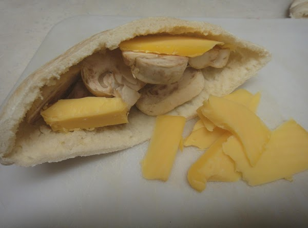 Place the pita on a cutting board and cut in half. Add the cheese,...