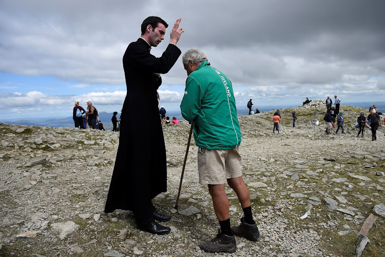 A pilgrim is blessed by the newly ordained Father Gerard Quirke after Mass at the summit of Croagh Patrick holy mountain during an annual Catholic pilgrimage near Lecanvey, Ireland.