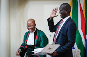 Chief Justice Mogoeng Mogoeng and cabinet minister Ronald Lamola share a light moment during the swearing in ceremony on Thursday.