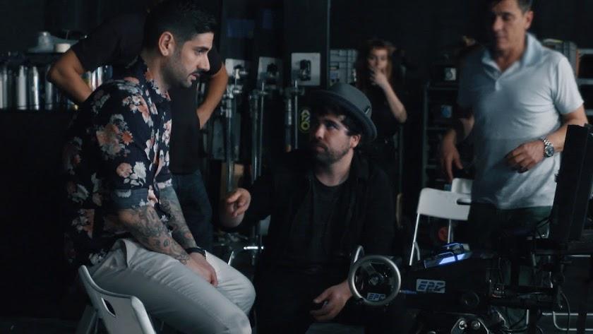 Willy Rodríguez conversa con el cantante Melendi durante la grabación de un videoclip del artista.
