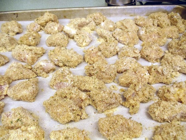Lay all the breaded chicken nuggets on a large platter before frying them; let...