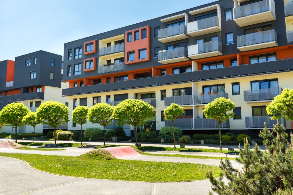 un bloc appartement et de condos à montréal de couleur noir rouge et jeune devant une rangée d'arbres en été