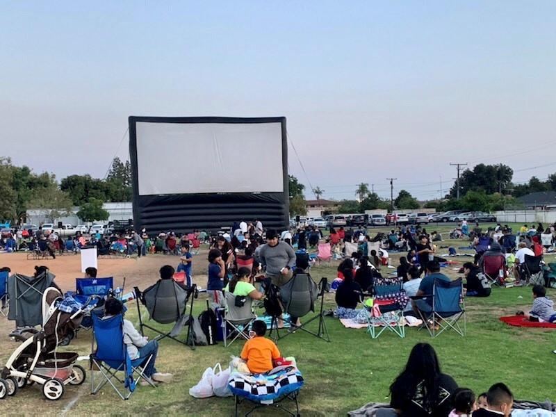 An image of the giant inflatable screen and the crowds surrounding it at a Movies in the Park event.