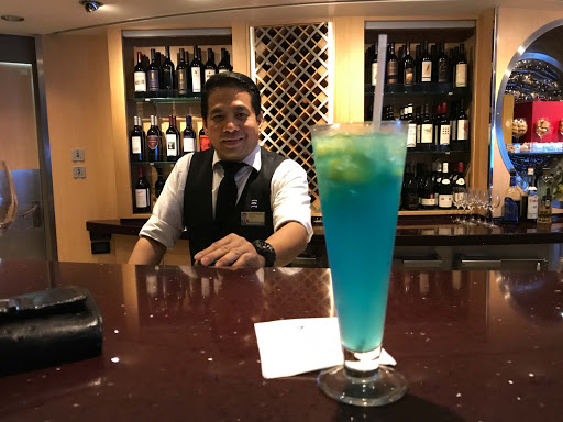 pinnacle-bar-cocktail.jpg - A friendly bar server poses with a blue cocktail in the Pinnacle Bar.