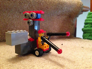 Photo: I know Lego is anti-violence so I'll clarify that the figure is holding flamethrowers to melt snow, at least that's what my kids tell me.  This is one of the early models and very simple. There are no adjustments on the pulleys. The brick sticking out the side helps level (roll axis) the vehicle as it travels down the zip line.