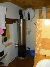 """Photo: """"zabydlená"""" koupelna a pohled na primitivní ohřívač vody, který používáme. Pár polínek, které hoří cca hodinu nám dají 100litrů 70°C vody, což máme tak na 2-3 dny. Na tuhle teplou vodu máme přes směšovací ventil nastavený na 40°C napojenou i pračku například... Pro případ lenosti máme i paralelně napojený elektrický ohřívač, ale ten jsme ještě nikdy nepoužili :)"""
