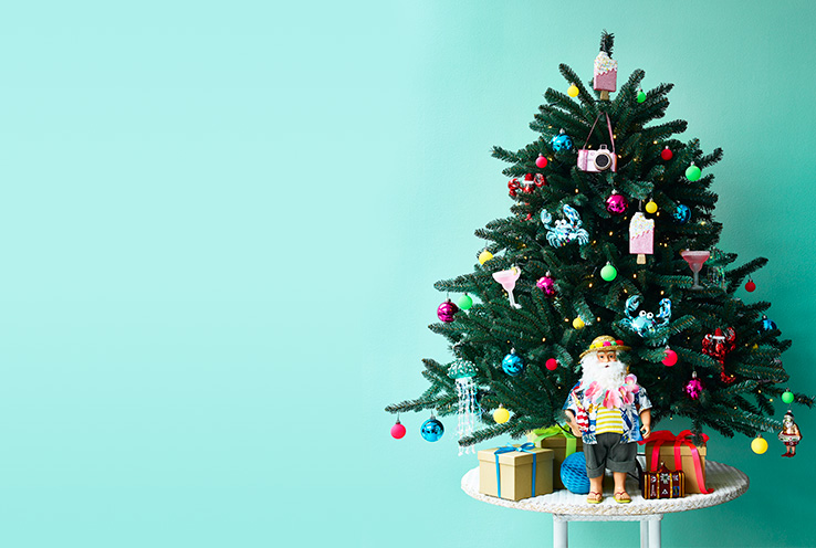 Christmas tree on a table with fun and colourful ornaments and baubles, including a Santa on vacation and jellyfish