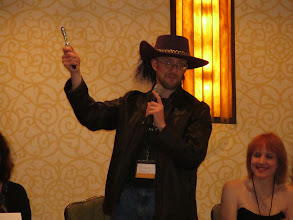 Photo: Jim Hines proves his worth as Toastmaster by out-epic-ing last year's - Howard Tayler.  Easy to do with your own Sonic Screwdriver and Epic Hat!  In a strange interdimensional coincidence, I own that hat in black.