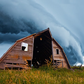 tornado forming behind old barn by John Wollwerth - Landscapes Cloud Formations ( stormy, nobody, twister, funnel, america, destruction, farmland, downdraft, supercell, landscape, storm, hurricane, farm, super, storm front, sky, nature, barn, dark, dramatic, weather, climate, rain, wind, ominous, thunderstorm, grass, green, cell, midwest, agriculture, damage, impending, tornado alley, dangerous, rural, country, field, horizontal, midlands, tornado )