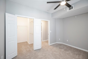 Bedroom with plush carpet, light gray walls, and ceiling fan