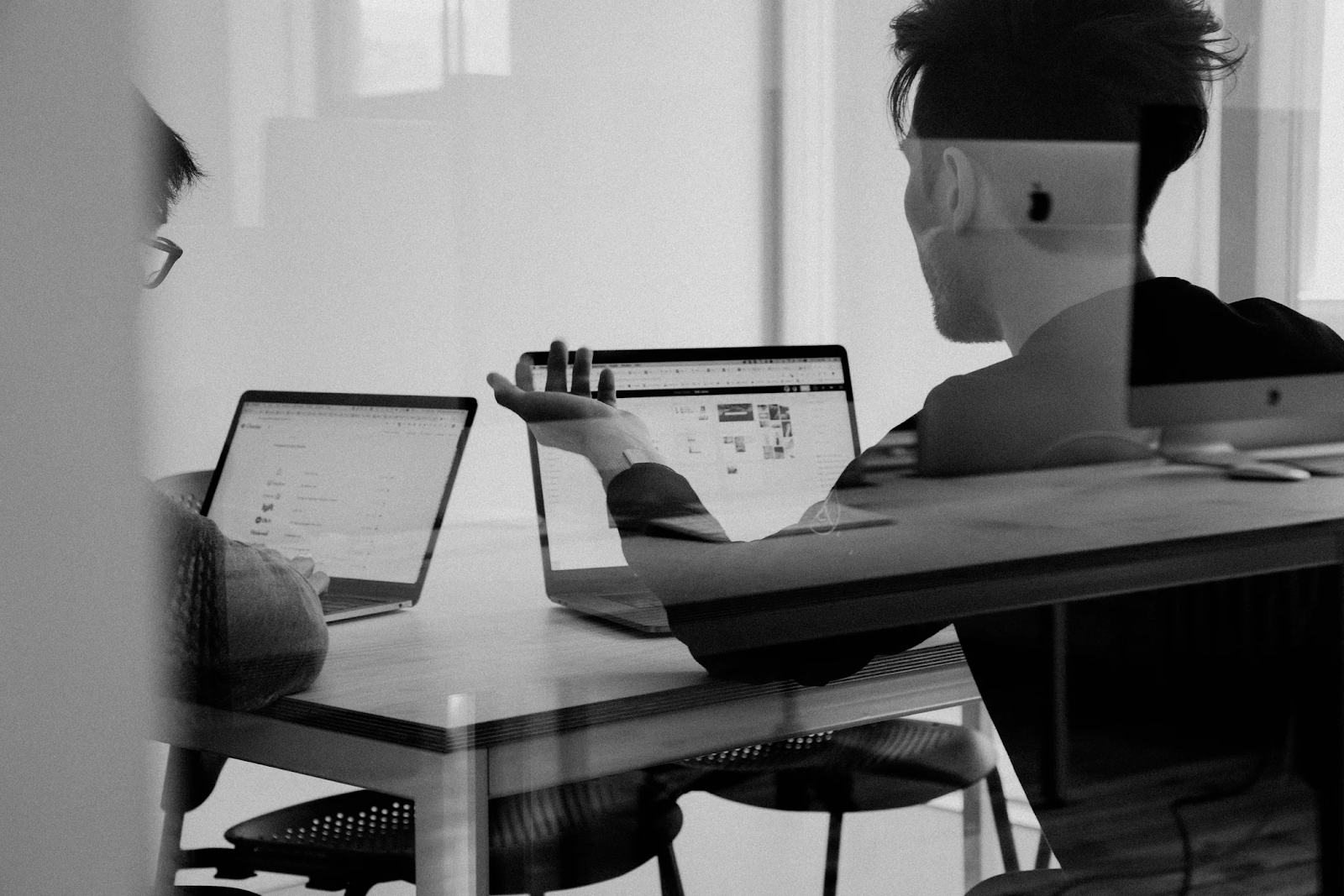 Two men using macbooks have a meeting to review and evaluate their designs.