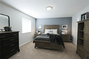 Bedroom with brown carpet, dark gray accent wall, large bed, and wood bedroom furniture