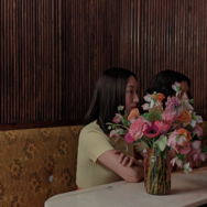 Two women sitting at a table, partially hidden behind a vase of flowers