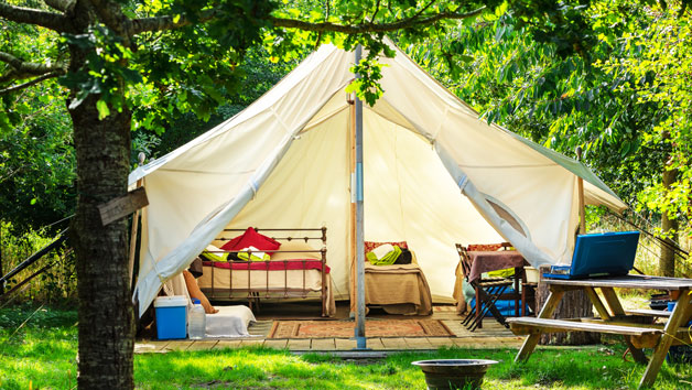 glamping tent with bed and furniture inside
