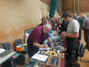 Photo: 008	The 7mm NG Association were present in force with their own 2nd Hand Sales, Products, Publications and of course Publicity. This view shows just the 2nd Hand Sales part of their stand, with Bob and Julie Cope busily helping customers to spend their cash .