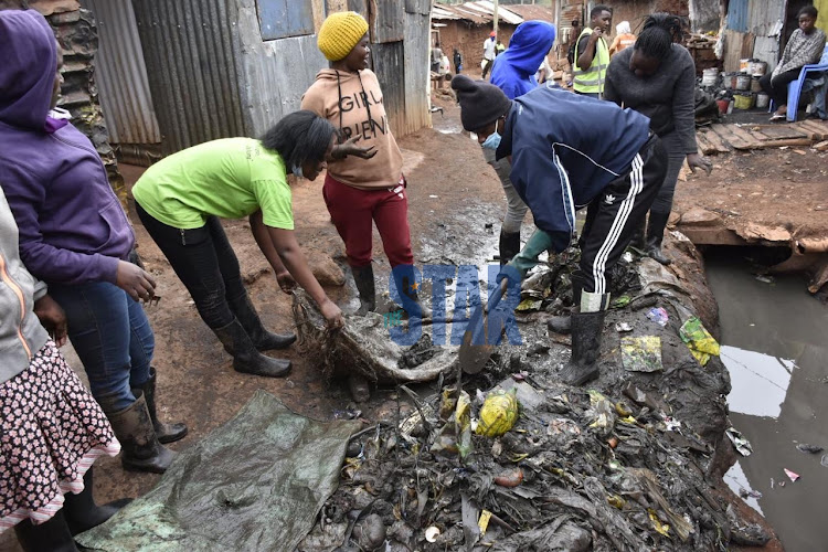 Youths from Nairobi's Kibera Katwekera take part in the Kazi Mtaani programme to clean up informal settlements on July 16.