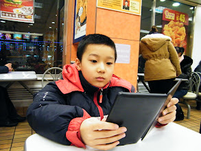 Photo: reunited son, warrenzh 朱楚甲 after blizzard I burst him for his loose management over his game gears from the bad influence his messy and fussy mom's. We treated ourself rich KFC, which also buffeted from supply scandal within China mainland market. here son reading his kindle before KFC served.