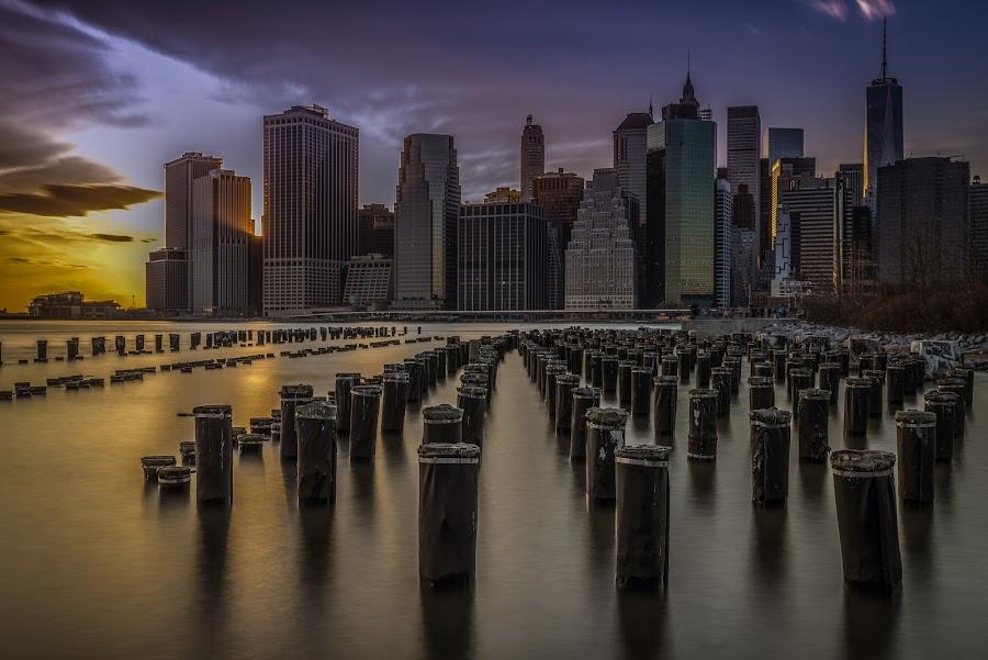 Sunset over Manhattan by Izzy Kapetanovic - City,  Street & Park  Skylines ( skyline, sunset, manhattan, cityscape, piles, pier 3, nyc, pilings, the sticks, brooklyn )