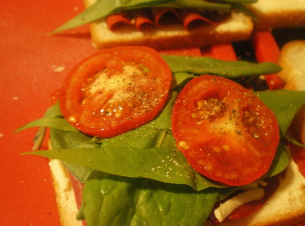 Top with sliced onion, cheese, arugula, and tomato.  Salt and pepper tomato if...
