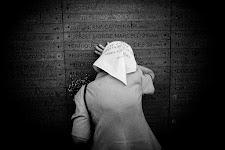 verdrietige vrouw voorover geleund tegen een wand met namen