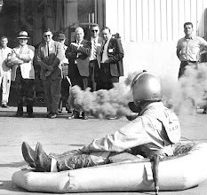 Photo: Ensign Jim Lund, assisted by Donald Gray, PR-2, demonstrates a PK-2 Life raft and survival equipment to members of the the South Texas Chamber of Commerce on their tour of Chase Field on April 22, 1959