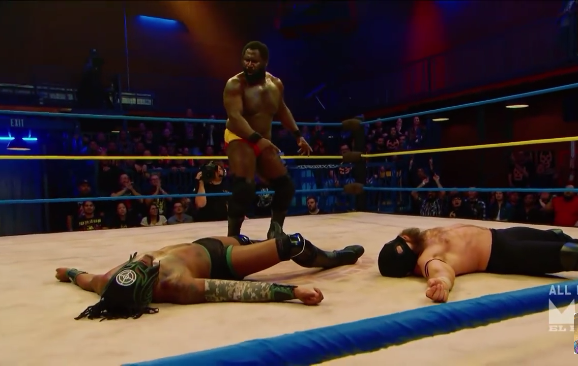 Screen cap from Lucha Underground. Mack (black man with a husky build and short hair) looks between his two team mates, Killshot and Son of Havoc, trying to decide which to pin.
