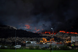 A fire rages at a tyre dump near a residential development in Sesena