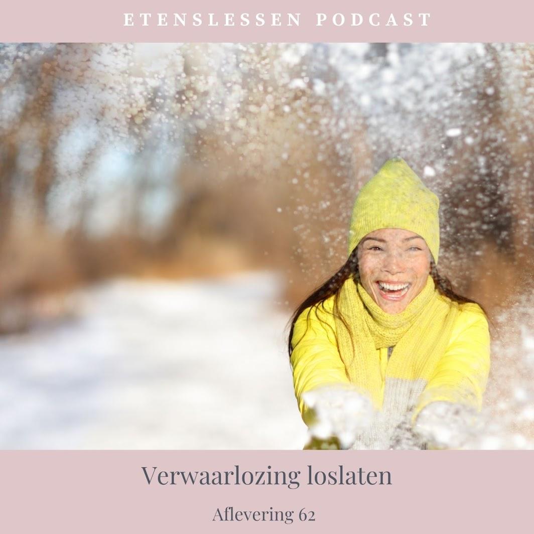 Blije vrouw in de sneeuw en kijkt in de camera. Ze gooit sneeuw omhoog