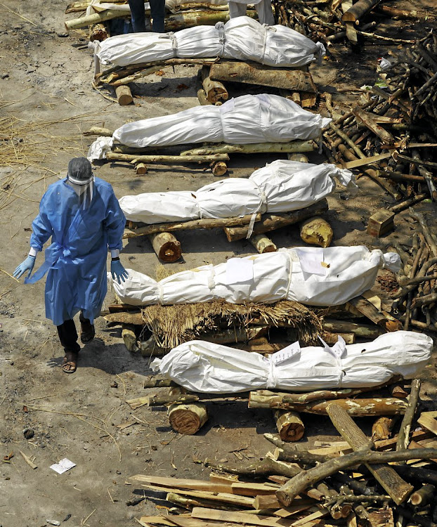 A health worker walks past a row of bodies of coronavirus victims waiting to be cremated in New Delhi.