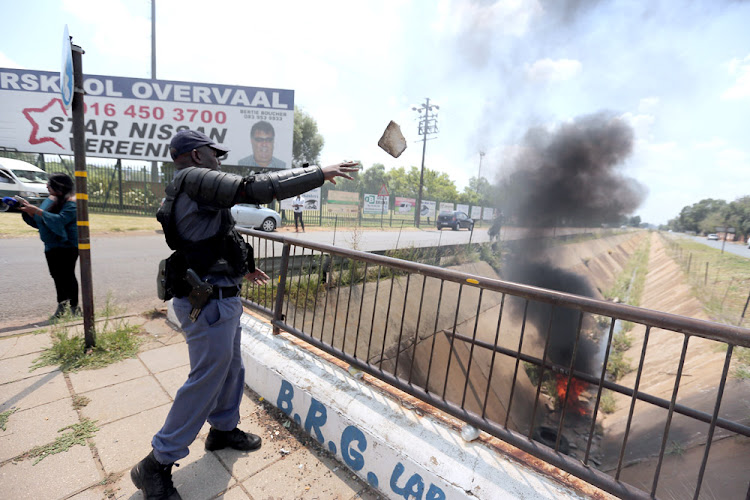 Members of the police clear barricades outside Hoerskool Overvaal in Vereeniging on the second day of protests there. Police have been removing barricades and monitoring the violent protest.