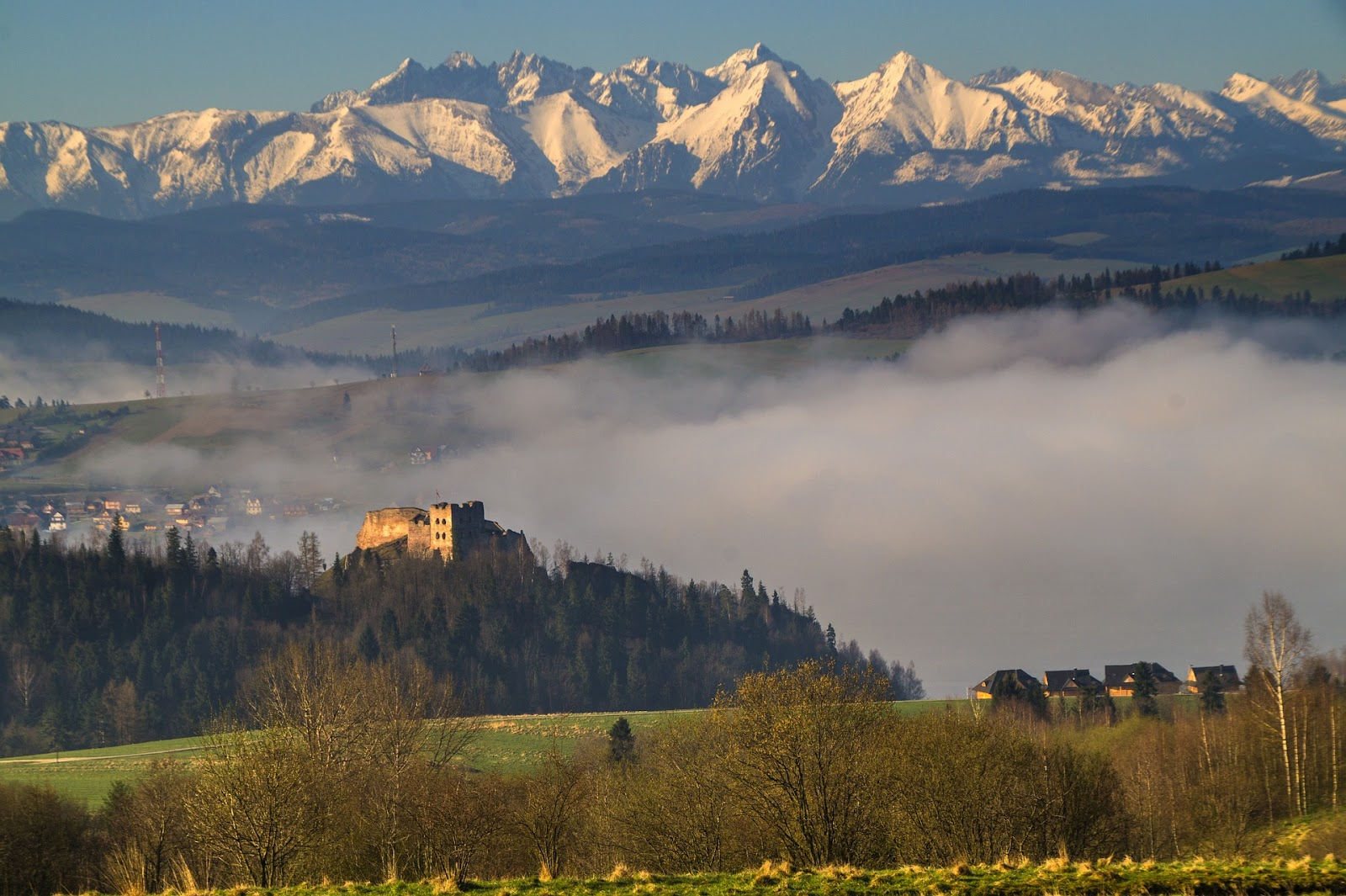 castle ruins in a cloudy forest with tall snow-covered tatry mountains in background during sunset in poland