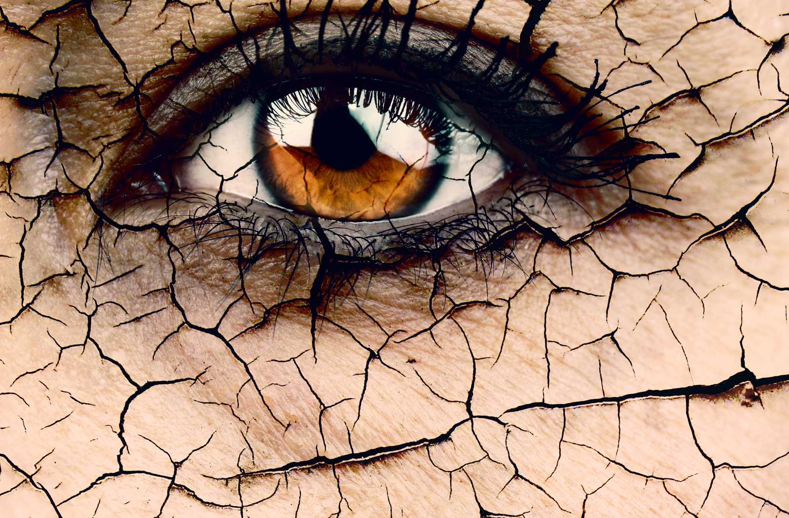 Illustration of dry eyes where the area of the face around the eye looks like cracked, dry earth