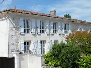 Photo: la façade, abritée derrière la verdure