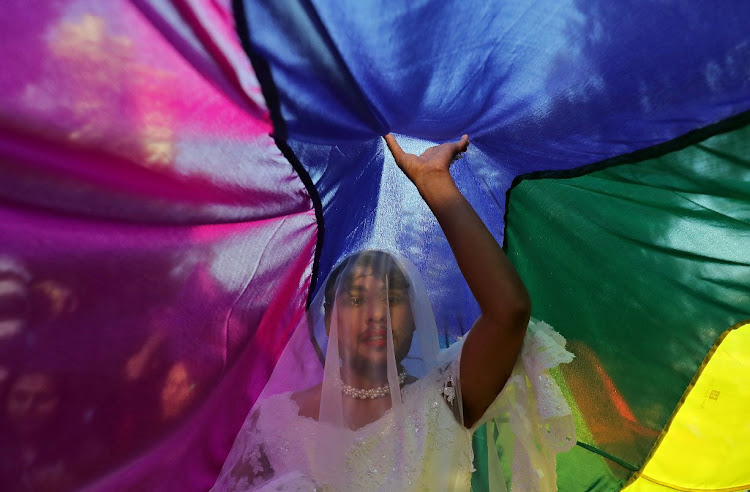 A participant touches a rainbow flag during Queer Pride March in New Delhi.